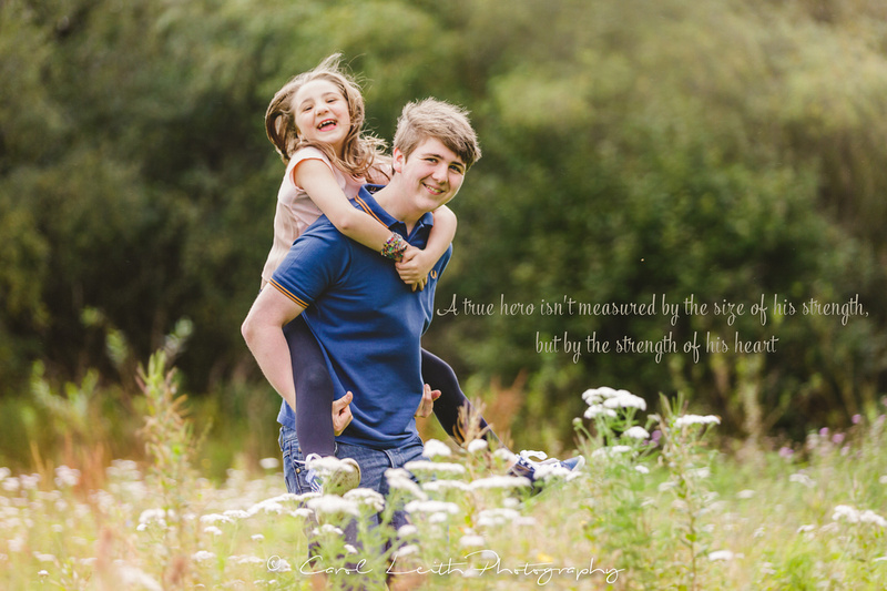 Brother and sister giving piggy back in a meadow